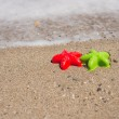 Two starfish-shaped molds on the sand — Stock Photo #49501191