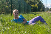 Young man lying on the green grass — Stok fotoğraf
