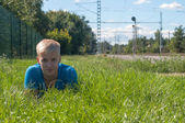 Young man in blue lying on the green grass — Stok fotoğraf