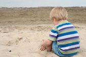 Little toddler boy sitting back on sandy beach — Stock Photo