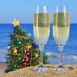 Glasses of champagne and Christmas tree on the beach - Stock Photo