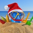 Christmas toys, decorations and Santa's hat on the beach — Stock Photo