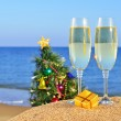 Glasses of champagne and Christmas tree on a beach - Stock Photo