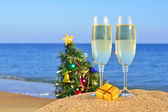 Glasses of champagne and Christmas tree on a beach — Stock Photo