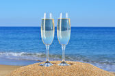 Glasses of champagne on the beach sand — Stock Photo