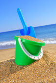 Baby bucket with sand and a shovel — Stok fotoğraf