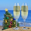 Seascape with glasses of champagne and Christmas tree on the bea — Stock Photo