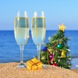 Glasses of champagne and decorated Christmas tree on the beach - Stock Photo