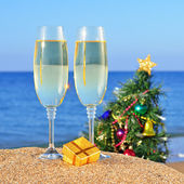 Glasses of champagne and decorated Christmas tree on the beach — Stock Photo