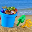 Christmas decorations in a baby bucket and toys on the beach — Stock Photo