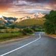 Stock Photo: Old highway against mountains at the sunset