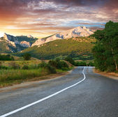 Old highway against mountains at the sunset — Stock Photo