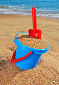 Baby bucket with sand and a shovel on the beach — Stock Photo