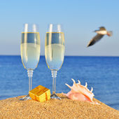Glasses of champagne, box with a gift and seashel — Stock Photo