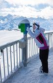 Une femme regarde à travers un télescope dans les montagnes — Photo