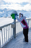 A woman looks through a telescope in the mountains — Stock Photo