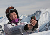 A woman photographs the skier himself smartphone — Stock Photo