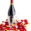 Bottle of wine with two glasses and rose petals on white.  — Zdjęcie stockowe