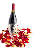 Bottle of wine with two glasses and rose petals on white. — Stock Photo