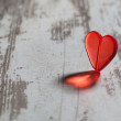 Red plastic heart on a white board — Stock Photo