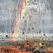 Rainbow on a rainy day. Rainbow through the wet glass. Drops on the glass. Радуга через мокрое стекло. — Stock Photo