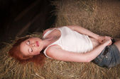 Woman lying on a haystack — Stock Photo