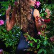 An attractive woman standing among the rose bushes — Stok fotoğraf