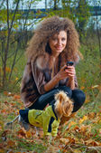 Pretty girl cuddling her dog in the woods — Stok fotoğraf