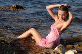 Frau sitzt am strand — Stockfoto