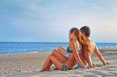 Lyckliga paret sitter på stranden — Stockfoto