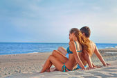 Szczęśliwa para siedzi na plaży — Zdjęcie stockowe
