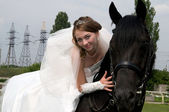 Fiancee in a wedding dress astride on a horse — Stock Photo