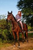At üstünde oturan kızıl saçlı kadın — Stok fotoğraf