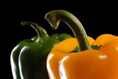 Green and yellow sweet pepper on a black background — Stock Photo