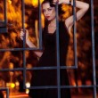 Pretty woman posing in cage outdoors at night — Stok fotoğraf
