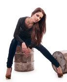 鉄バレルの上に座ってのジーンズの女の子 — ストック写真