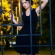 Pretty woman posing in cage outdoors at night — Stock Photo