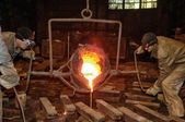 Foundry - molten metal poured from ladle into mould — Stock Photo