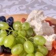 Grapes and cheese on plate — Stock Photo
