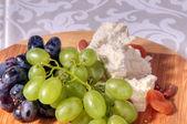 Winogrona i ser na talerzu — Zdjęcie stockowe
