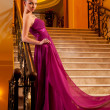 Woman in a beautiful dress sloit on the stairs — Stock Photo #7823031