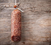 Hanging salami sausage on wooden background — Stok fotoğraf