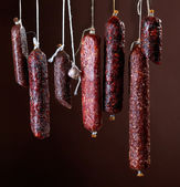 Various hanging salami sausages — Stock Photo
