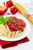 Portion of spaghetti bolognese with green basil leaf on white pl — Stock Photo