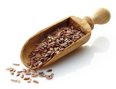 Wooden scoop with flax seeds — Stock Photo