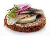 Brown bread canape with anchovies decorated with red onion and d — Stock Photo