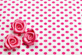 Polka dot paper and pink decorative roses — Stock Photo