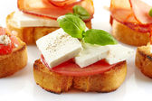 Toasted bread with fresh goat cheese and tomato — Stockfoto