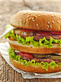 Burger on wooden table — Stock Photo