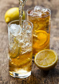 Pouring iced tea with lemon — Stock Photo